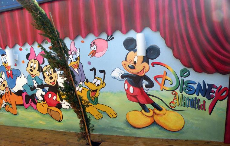 ציורים של דמויות שונות על קיר בגן ילדים