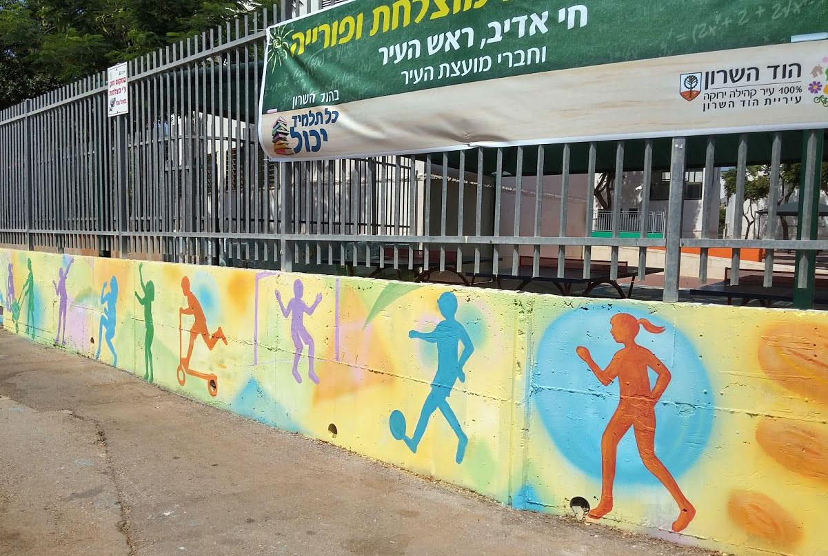 ציור של ילדים וספורט על הגדר החיצונית של בית הספר