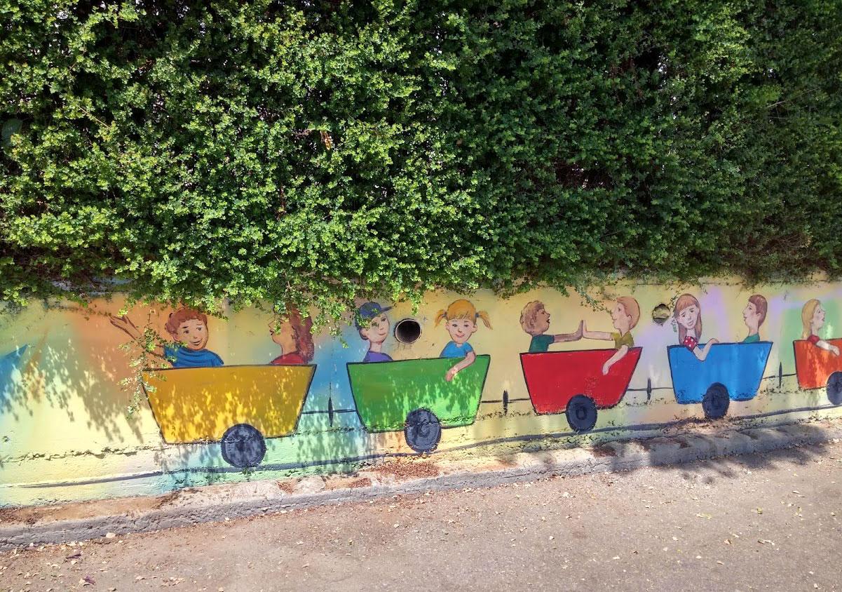 ציור של רכבת על הגדר של בית ספר