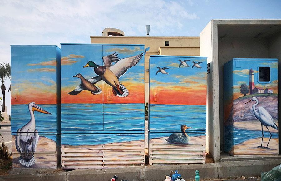 ציור של ציפורים על ארבע ארונות חשמל