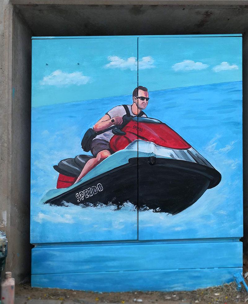 ציור על ארון חשמל של איש על סירת מנוע