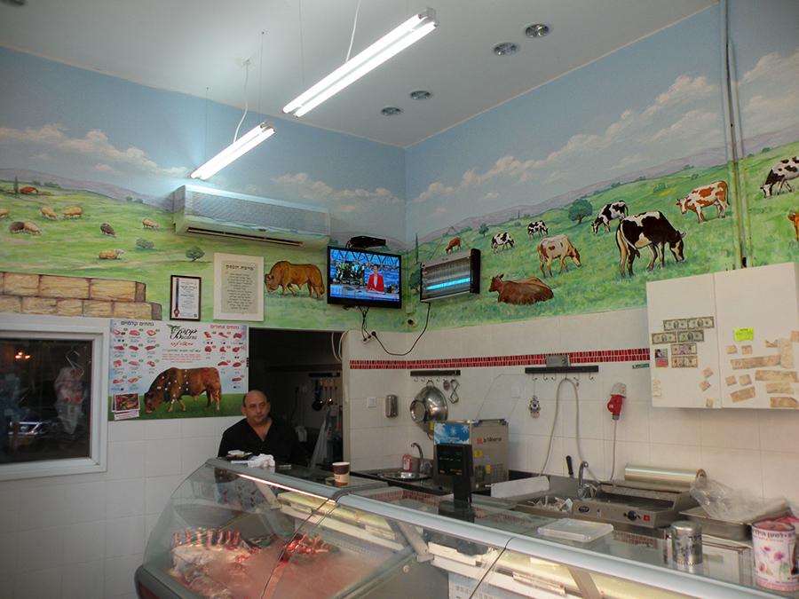 ציורי קיר לאטליז של פרות וכבשים רועות על הדשא