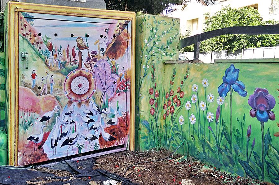ציורי קיר של פרחים ותמונה על ארון חשמל בחצר הבית
