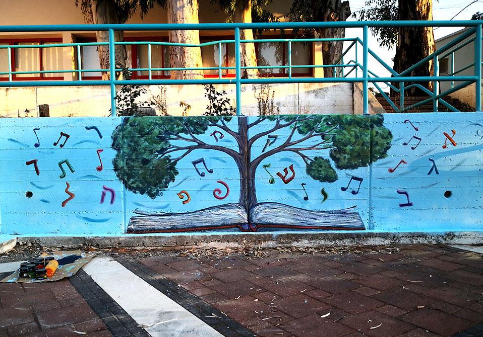 ציור קיר חיצוני של תווים ועץ בספרייה בתל מונד